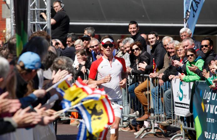 Huub van Noorden aan de finish van de Marathon van Zeeuws-Vlaanderen. Hij droeg een pet en zonnebril tegen de felle zon.