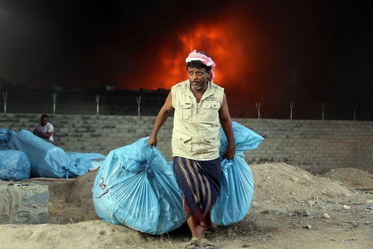 Zakken vol met voedsel worden weggesleept uit het United Nations World Food Programme warenhuis in Yemen door een werknemer. Beeld ANP