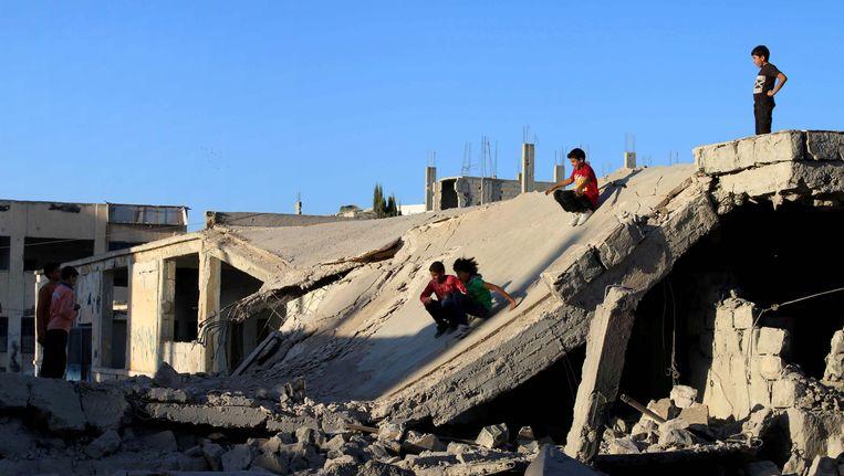 Kinderen glijden van een brokstuk van een kapotgeschoten huis in Daraa, in het zuidwesten van Syrië. Beeld afp