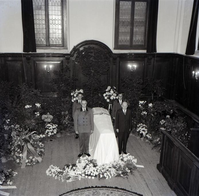 De opgebaarde koningin Wilhelmina in de kapel van Paleis Het Loo; niet met een kroon, maar met een bijbel op de kist. Vier punaises in de vloer van de kapel geven nu nog steeds de plaats aan die de dodenwacht had ingenomen.