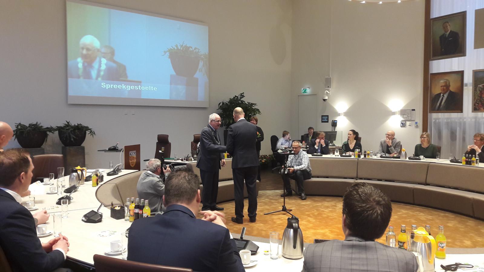 De installatie van de gemeenteraad in Loon op Zand vorige week; raadsnestor Bertus Kemmeren (met ambtsketen) heeft net Gerard Bruijniks (op de rug) van GemeenteBelangen geïnstalleerd als raadslid en feliciteert hem.