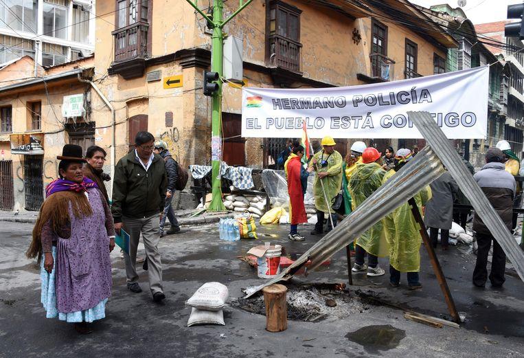 Bolivianen blokkeren een straat in La Paz met een spandoek waarop zij hun steun aan de politie uitspreken. Beeld AFP