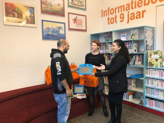 Farida Topan (rechts) en Dianne van Erp van Welzijn De Meierij reiken de eerste Ipad met taalapps uit.