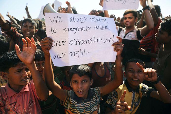 Een jongetje houdt een protestbordje omhoog in een opstand in een vluchtelingenkamp in Bangladesh.