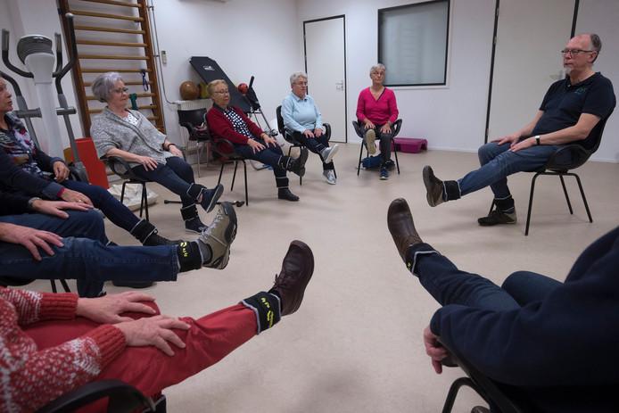 Rechts doet fysiotherapeut Jaap Sneep de oefening voor. De oudste deelnemer Ilse Duin (86) zit derde van rechts.