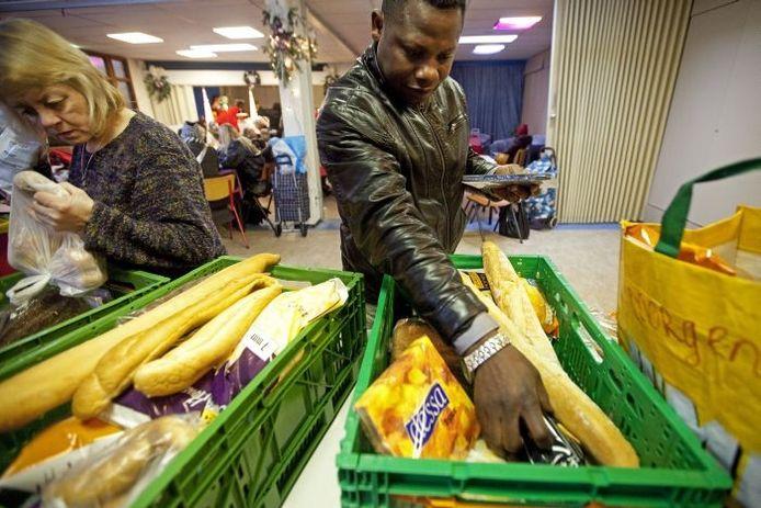 Klanten van de voedselbank halen hun voedselpakketten op. Foto: ANP