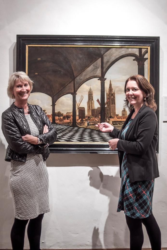 Anita Jansen (l) en Janelle Moerman bij het schilderij 'Gezicht op Delft met een fantasieloggia' van Daniël Vosmaer, een tijdgenoot van De Hooch.