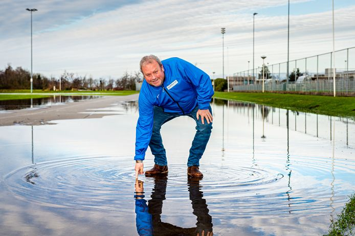 Secretaris Bert Timmerman van IJsclub Vooruitgang in Ammerstol voelt symbolisch de temperatuur van het water. De ijsbaan wordt momenteel gevuld met water.