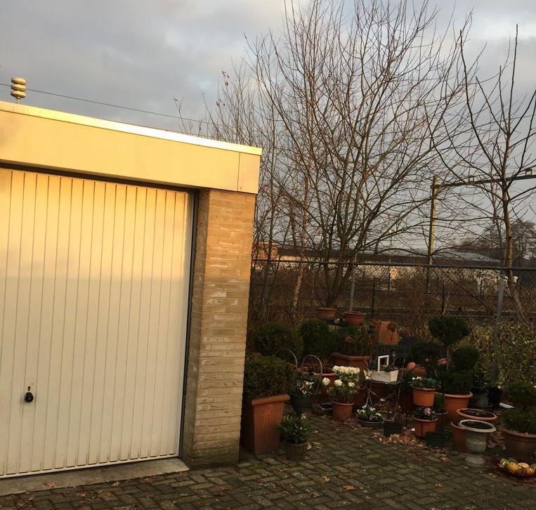 Hun garage met tuintje aan het spoor Beeld