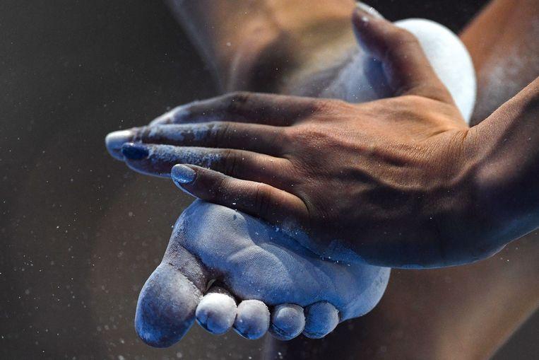 De Britse Georgia-Mae Fenton prepareert haar voeten met magnesium voor de oefening op de evenwichtsbalk tijdens de Europese Spelen in Minsk. Beeld AFP