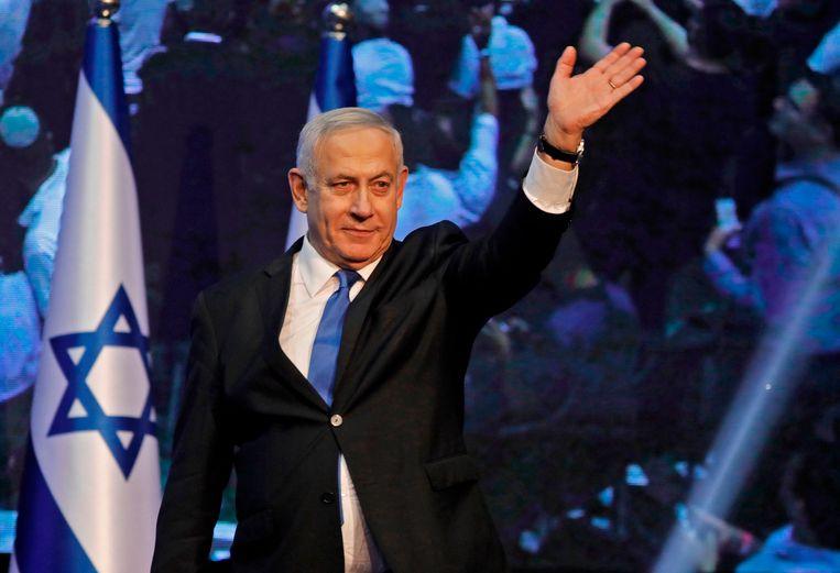 Benjamin Netanyahu zwaait naar zijn aanhangers op een verkiezingsbijeenkomst.   Beeld AFP
