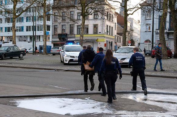 Nabij de loods wordt een man geboeid weggebracht door de politie.