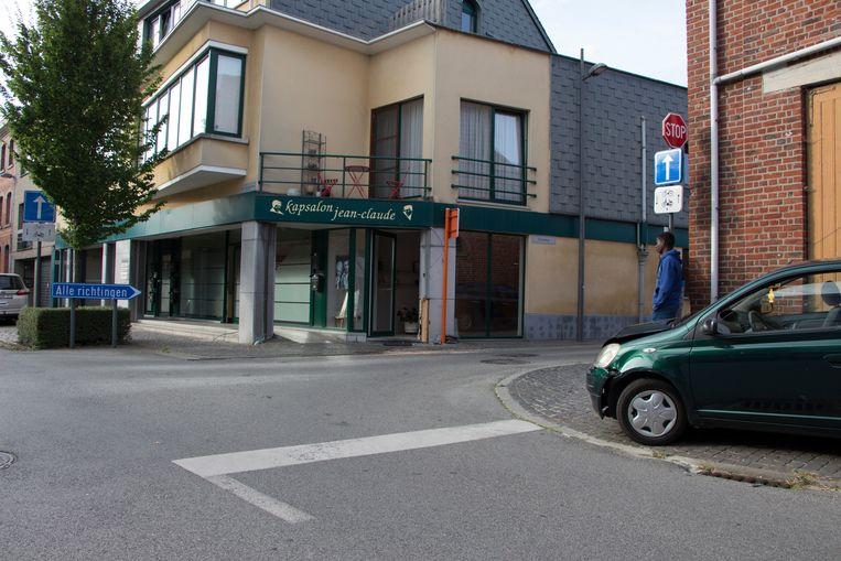 Het kapsalon, met rechts de auto. De blauwe steen aan de ingang brak los (inzet).