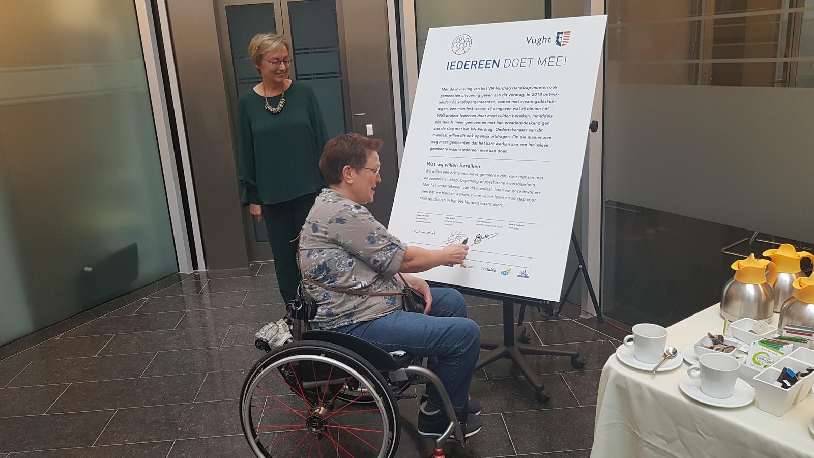 Voorzitter Elise Adriaanse van Toegankelijk Vught' tekende het Manifest 'Iedereen doet mee!' Wethouder Saskia Heijboer kijkt mee