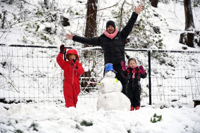 Papa en dochtertjes maken een sneeuwpop in Holsbeek.