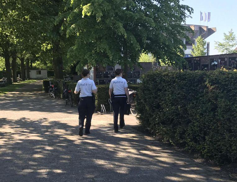 Politieagenten gaan na of er schade is op het kerkhof.