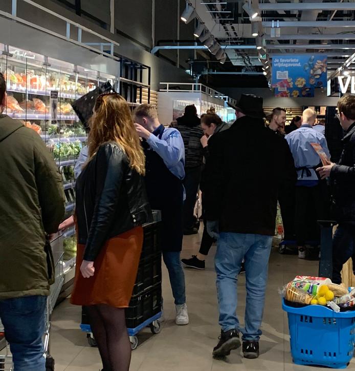 Klanten drommen samen in de AH-supermarkt in Kampen, tot grote ergernis van burgemeester Bort Koelewijn.