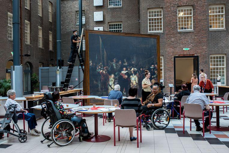 De bewoners van het Dr. Sarphatihuis in Amsterdam krijgen 'een rondleiding' (vanuit hun stoel).  Beeld Nosh Neneh