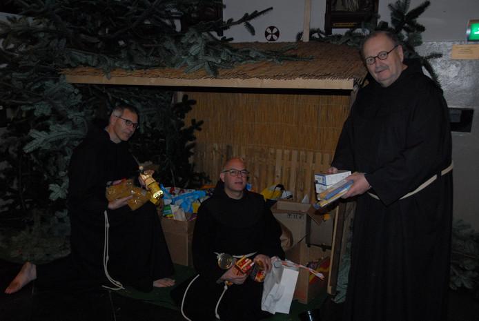Drie trotse broeders bij de met levensmiddelen gevulde kerststal: de broeders Roland, Rangel en Hans