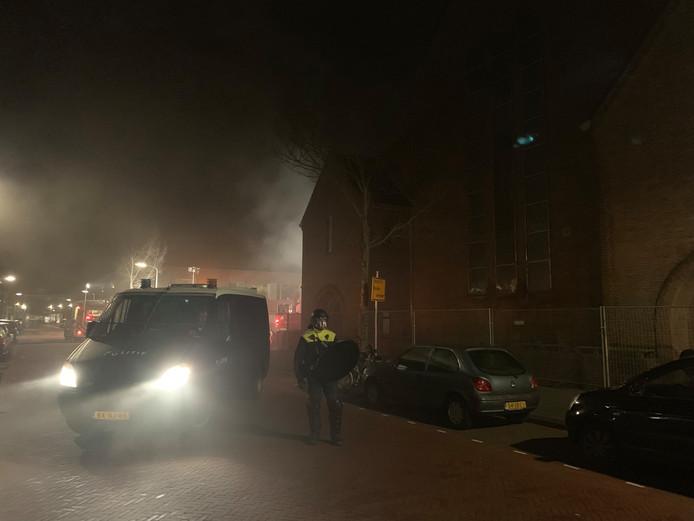 De ME bewaakt de Pnielkerk, vlakbij vloog een container in brand