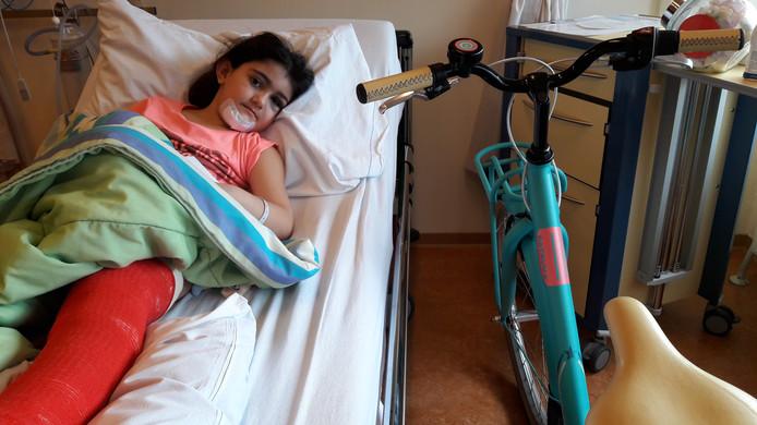 Basma, nog op bed door haar gebroken been, met haar nieuwe fiets.