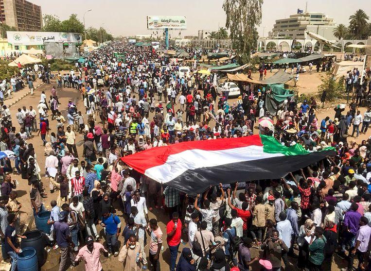 Soedanese demonstranten met de nationale vlag bij het militaire hoofdkwartier in hoofdstad Khartoem.  Beeld AFP