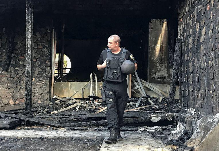 Een politieagent kijkt rond bij geblakerde resten van het huis van de voormalige president van de Oekraïense centrale bank, Valeria Hontareva. Volgens Hontareva werd de brand aangestoken als wraak voor de nationalisatie van een van de grootste banken van het land in 2016. Beeld REUTERS