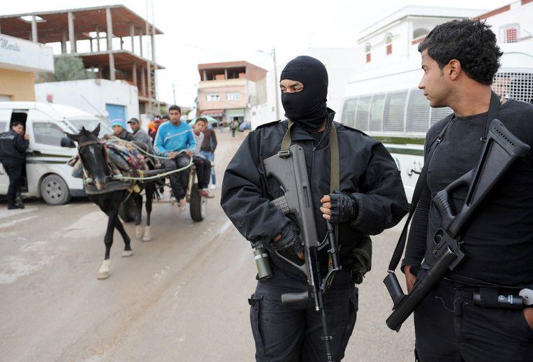 Twee gewapende agenten houden in 2012 de wacht bij een moskee in de armenwijk Douar Hicher. In die tijd gingen veel jongeren naar Syrië. Nu niet meer. Beeld Fethi Belaid / AFP