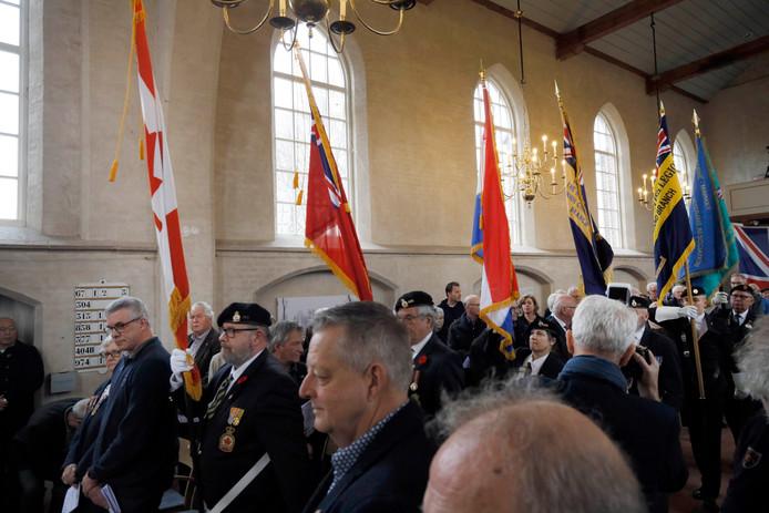 De vaandels van de verschillende geallieerden krijgsmachtonderdelen worden tijdens de herdenking de kerk in gedragen.