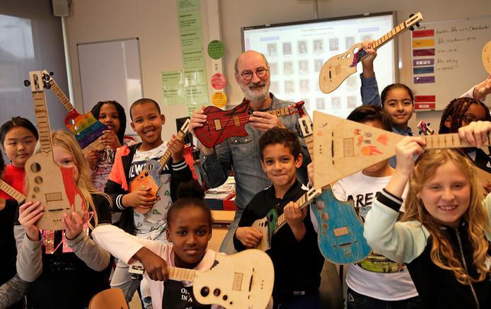 De leerlingen van De Piramide en 'meester' Jos tonen hun zelfgemaakte gitaartjes.