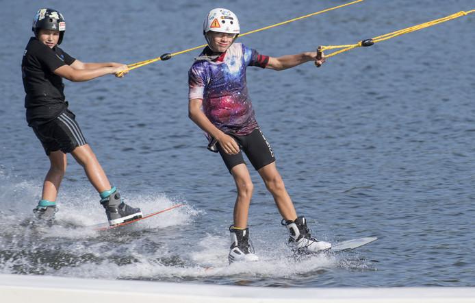 Lucas ter Weele (onder 15, witte helm) en Khan Bulut (onder 11, zwarte helm) uit Enschede mogen zich Nederlands kampioen wakeboarden noemen.