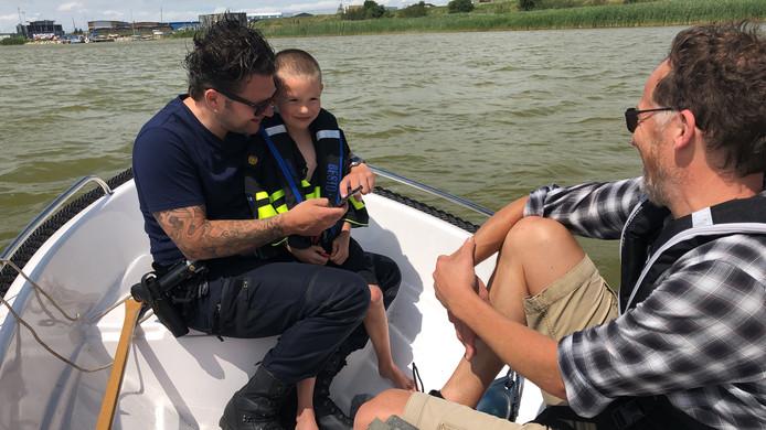 De vijfjarige Sasha Rast staat te klappertanden als hij aan boord klimt van de patrouilleboot. Hij krijgt het politieshirt van wijkagent Michael Verdult.