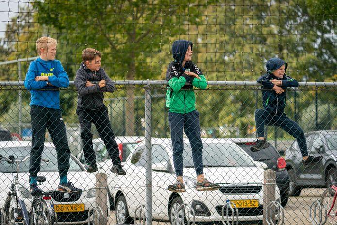 Jeugdige Spero-supporters bekijken de thuiswedstrijd van hun eerste elftal tegen Concordia Wehl noodgedwongen van achter de hekken. Het sportpark is dicht voor de 'niet-voetballers'.