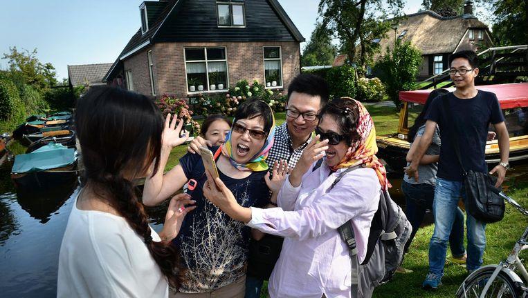 Chinese toeristen hebben plezier bij een bezoekje aan Giethoorn. Beeld null