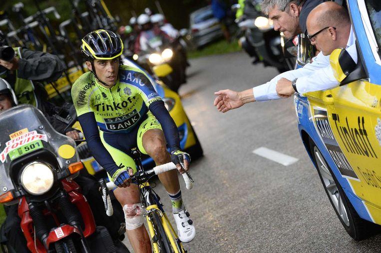 Bjarne Riis probeert Alberto Contador een handje te helpen in de Tour van 2014. In 2015 was het de eerste keer in twingtig jaar dat Bjarne Riis geen onderdeel uitmaakte van de Tour. Beeld anp