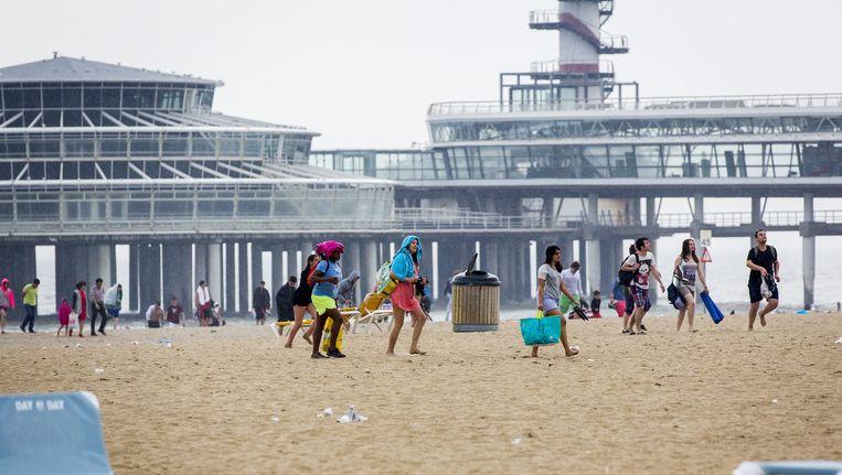 Strandgangers passeren de Scheveningse pier. Beeld anp