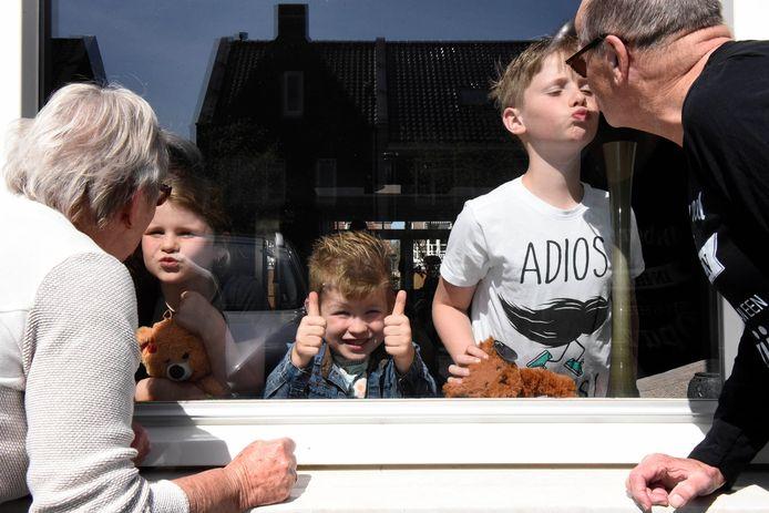 Hans en Corrie van der Vlist gaan even op raambezoek bij hun hun kleinkinderen Olaf, Julie en Finn.