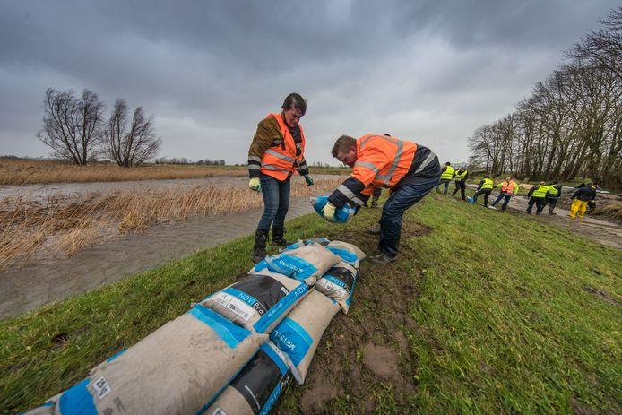 Storm in Nederland. Op de Mandjeswaard/Kampereiland werd voor het eerst de KEI-brigade ingezet om de dijk te verstevigen met (metsel) zandzakken.