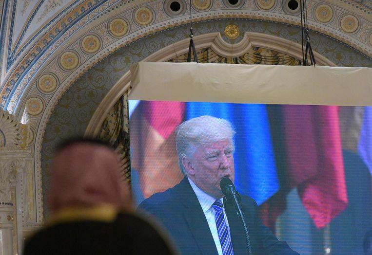 Een Saoediër kijkt naar de toespraak van Trump in Riyad. Beeld afp