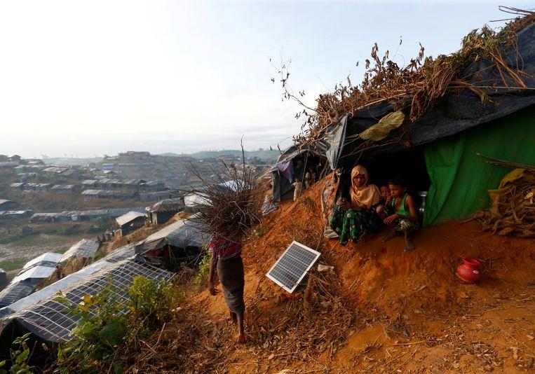 Rohingya vluchtelingen zitten buiten hun schuilplaats op een heuvel in de buurt van Cox's Bazar.  Beeld REUTERS