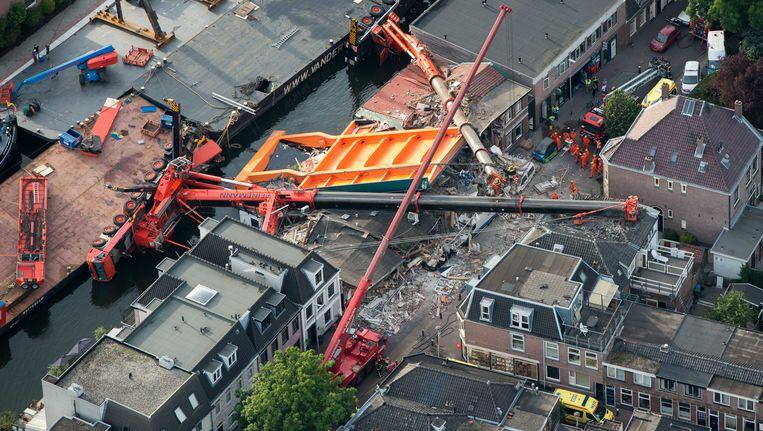 Luchtfoto van de plek aan de Hooftstraat waar twee bouwkranen met een brugdek op een aantal woningen zijn gevallen. Beeld anp