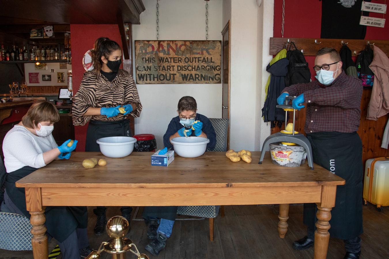Daphne en Ko schillen de aardappelen terwijl Joram ze door de frietsnijder haalt. Petra de Winter (staand) kijkt toe.