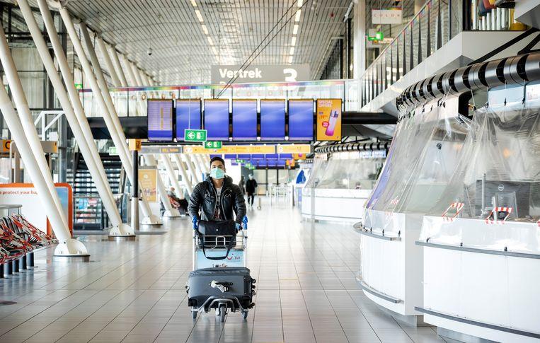 Een passagier met mondkapje in een verlaten vertrekhal op Schiphol. Beeld ANP