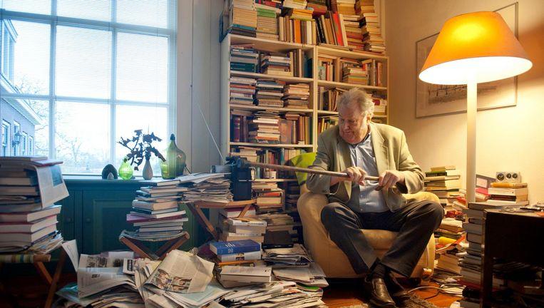Brands te midden van zijn collectie boeken en kranten. 'Denk je dat de balken het houden?' Beeld An-Sofie Kesteleyn / de Volkskrant