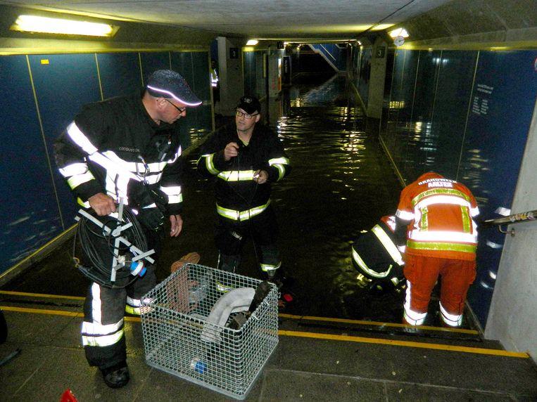 De brandweer pompt de voetgangerstunnel onder het station van Aalter leeg.
