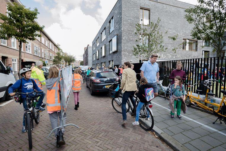 Tijdens haal- en brengtijden is de straat voor Montessorischool De Abeel in Den Haag afgesloten voor auto's.  Beeld Inge Van Mill