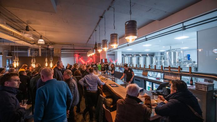 Drukte op besloten openingsfeestje van Puik Bieren in Apeldoorn. Door de glazen wand is rechts de brouwerij zichtbaar. De publieksopening is op  maart.