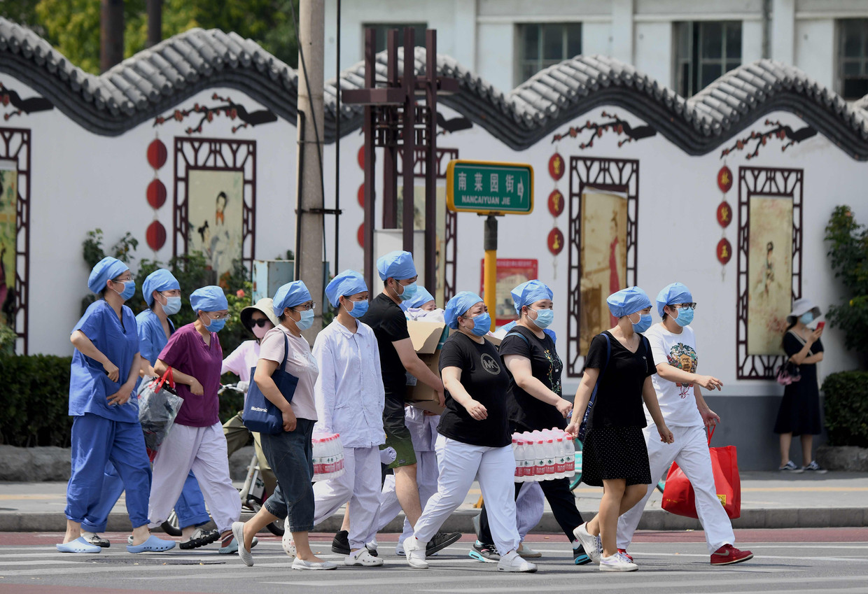 Medisch personeel arriveert bij een testlaboratium in Peking, dat opschaalt vanwege een corona-uitbraak op een markt in de Chinese hoofdstad.   Beeld AFP