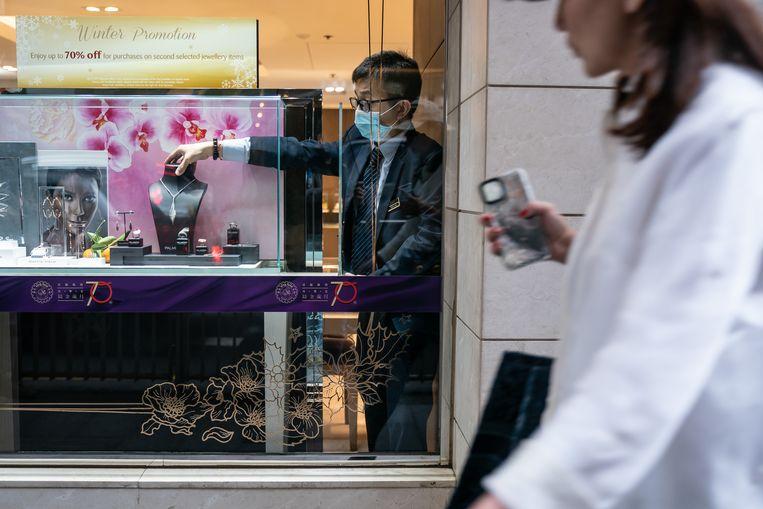 Een werknemer van een juwelierszaak in Hongkong draagt een mondkapje. Het verkeer tussen Hongkong en China is drastisch beperkt.   Beeld Getty