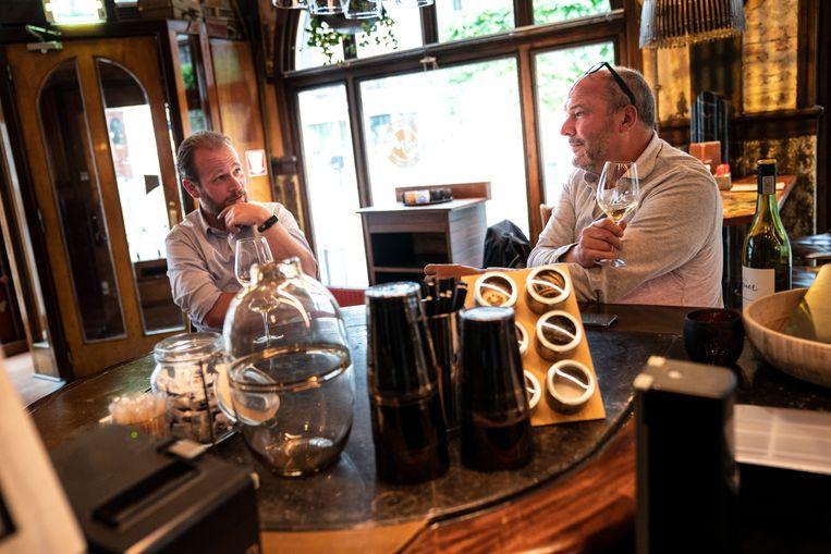 Joost van Keulen (links) is heel blij dat de café 's weer open gaan, hier in gesprek met horecabaas Patrick Beijk in Mr Mofongo in Groningen. Beeld Reyer Boxem